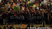 Protesters hold a banner that reads Climate justice (Getty Images/AFP/G. Bouys)