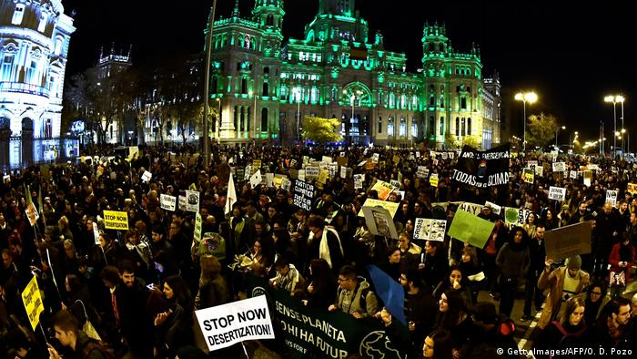 Demonstrators walk past the city hall on Cibeles Square during a mass climate march to demand urgent action on the climate crisis