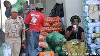People browse at an outdoor fruit and vegetable market in South Africa