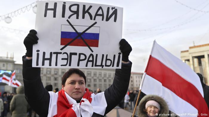 A protester holds a banner reading 'No to integration!' during a rally in downtown Minsk
