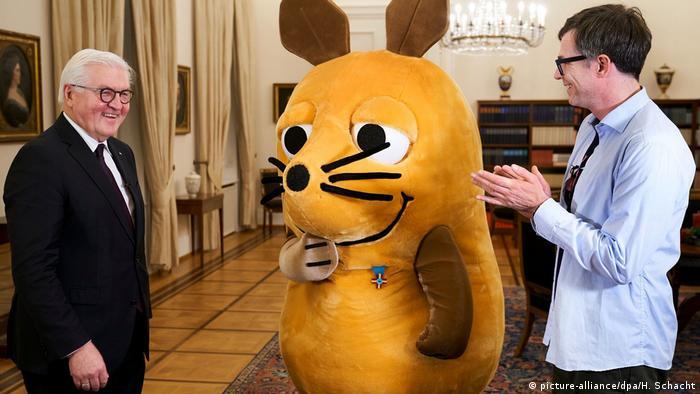 Мышь с важной наградой во дворце федерального президента Германии вместе с главой государства Франком-Вальтером Штайнмайером и ведущим программы Ральфом Касперсом (Ralph Caspers), который в этот день тоже получил самый настоящий орден