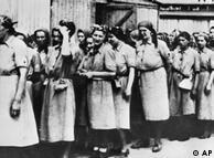 کسانی که بعد از مرحله گزینش زنده میماندند، باید به کار جانفرسا مشغول میشدند. این عکس زنان را در صف برای کار نشان میدهد و توسط یک نگهبان اس اس گرفته شده است.