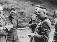 اینها مسئولین اصلی جنایت در آشویتس بودند: سمت چپ ریشارد بر، که از ماه مه ۱۹۴۴رییس آشویتس بود. در کنار او دکتر یوزف منگله و یکی از فرماندهان آشویتس به نام یوزف کرامر که فقط نیمی از چهرهاش پیدا است، قرار گرفتهاند. رودلف هوس، فرمانده سابق آشویتس، نیز در کنار آنان دیده میشود. هویت مردی که سمت راست قرار گرفته، مشخص نیست. این عکس در سال ۱۹۴۴ گرفته شده است.
