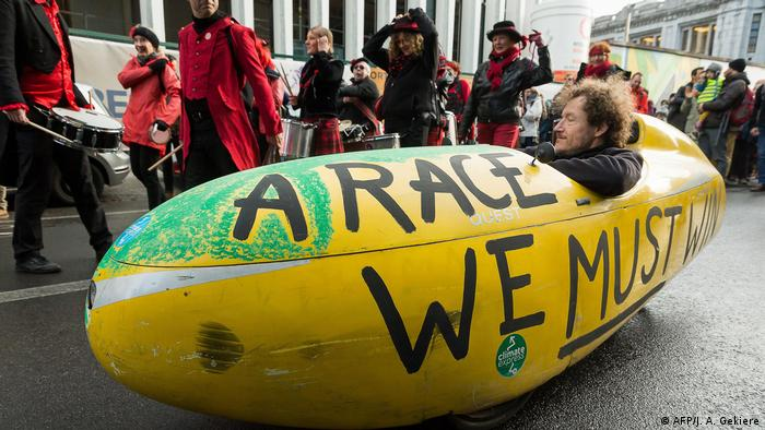 A man at a protest in a yellow vehicle emblazoned with the words a race we must win