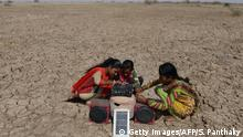 This picture taken on April 7, 2017 shows Indian salt pan worker Puja Ganeshbhai Muladiya (R) along with her sisters prepare for a traditional Garba (Gujarat's folk dance) as they connect a solar panel-powered music systems in the Little Rann of Kutch (LRK) region of Gujarat some 180km west of Ahmedabad. Indian salt pan workers of the Agariya community in Gujarat work in the remote and arid Little Rann of Kutch (LRK) region for nearly eight months of the year during the salt farming season. India is ranked third in gross amount of salt produced in the world, behind China and the United States, and the western state of Gujarat accounts for 77 percent of India's production. -- Sheltered beneath a canvas sheet to escape the blistering desert sun, miles from any roads or power lines, a group of Indian children huddle around a digital tablet and experience the internet for the very first time. The remote wi-fi connection is powered by a van bringing the digital world to around 10,000 families living on the inhospitable salt flats of western Gujarat, where they work eight months a year in extreme conditions. / AFP PHOTO / SAM PANTHAKY / TO GO WITH AFP STORY India-education-NGO (Photo credit should read SAM PANTHAKY/AFP via Getty Images)