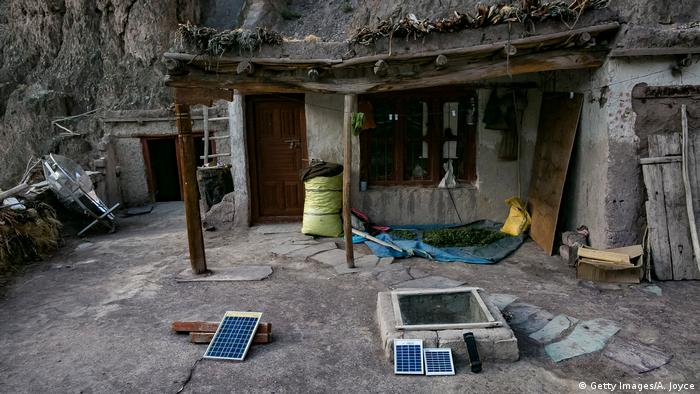 Houses built into the mountain. On the ground outside are three small solar panels