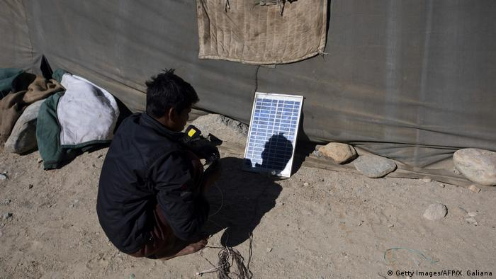 A man sits in front of a single solar panel by the side of a dusty road