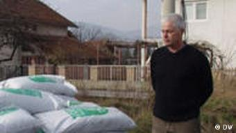 Man standing by the side of pile of sacks of organic fertilizer