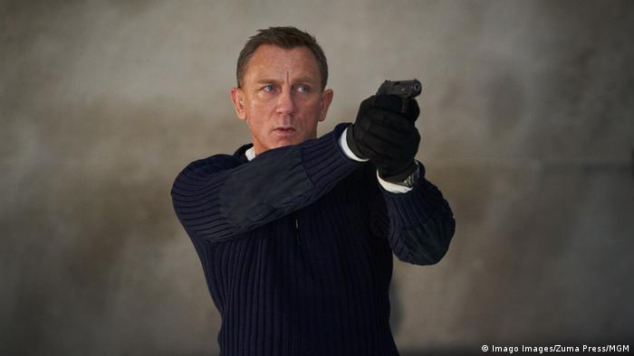 Daniel Craig dressed as James Bond holds up a gun (Imago Images/Zuma Press/MGM)