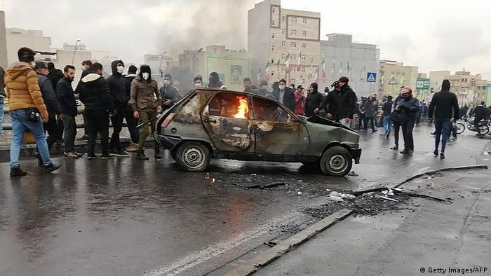Iranian protesters gather around a burning car during a demonstration against an increase in gasoline prices in the capital Tehran (AFP)