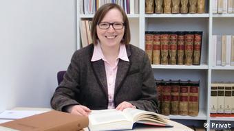 Christine Siegert at her desk, book opened, bookshelf at rear