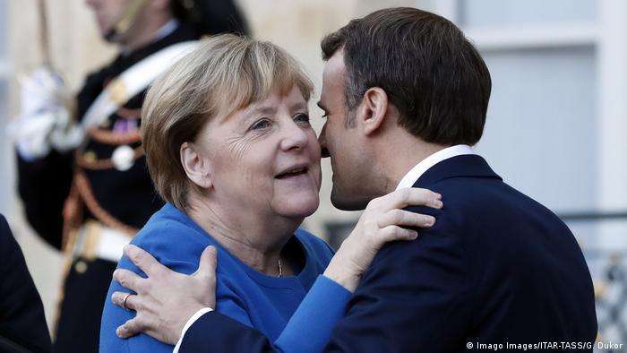 Angela Merkel embraces Emmanuel Macron