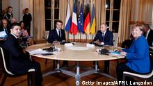 Zelenskiy, Macron, Putin and Merkel sitting around a table