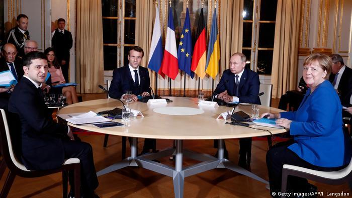 Zelenskiy, Macron, Putin and Merkel sitting around a table