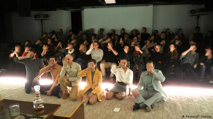 Actors and the audience hold up their hands at Budapest's Trafo theater in protest against the Hungary's government law