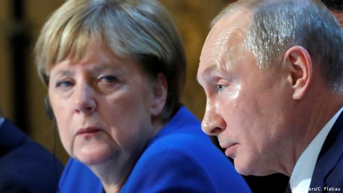 Angela Merkel and Vladimir Putin sitting next to one another in Paris in 2019