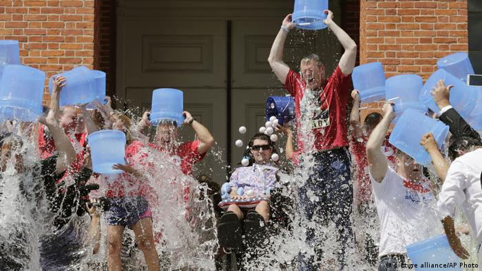 In this Aug. 10, 2015, photo, Massachusetts Gov. Charlie Baker, right center, and Lt. Gov. Karyn Polito, third from left, participate in the Ice Bucket Challenge with its inspiration Pete Frates, seated in center