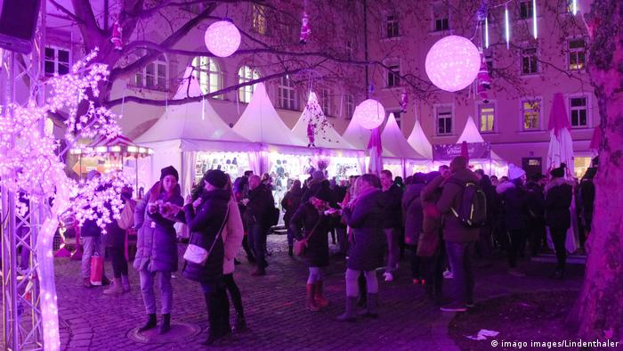 Germany | Pink Christmas market in Munich - people standing at ight in pink illumination (imago images/Lindenthaler)