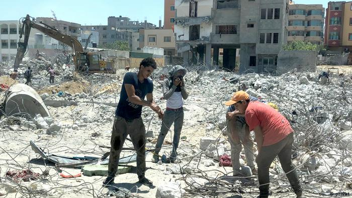 Men clear out rubble in Gaza