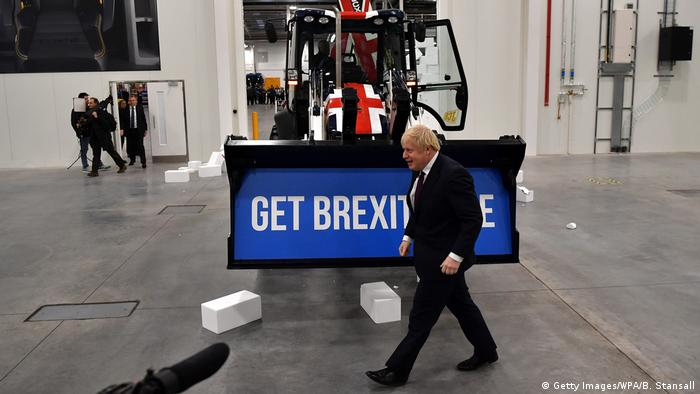 Boris Johnson walks in front of a digger with the slogan Get Brexit done