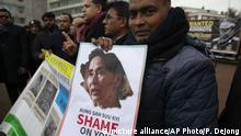10.12.2019*** Demonstrators gather for a picture around a truck with a picture of Myanmar's General Min Aung Hlaing, and a text reading Wanted for Genocide Against Rohingya, rear, outside the International Court of Justice in The Hague, Netherlands, Tuesday, Dec. 10, 2019. Myanmar's leader Aung San Suu Kyi will represent Myanmar in a case filed by Gambia at the ICJ, the United Nations' highest court, accusing Myanmar of genocide in its campaign against the Rohingya Muslim minority. (AP Photo/Peter Dejong)  