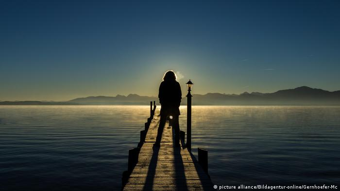 Silhouette of a peson standing on a jetty at Lake Chiemsee at sunset