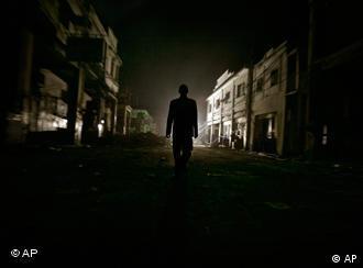 Ein Mann geht nachts durch eine zerstörte Straße von Port-au-Prince (Foto: AP)