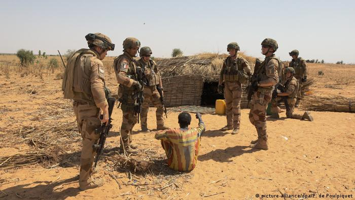 A group of troops speak to a man in a small village in West Africa