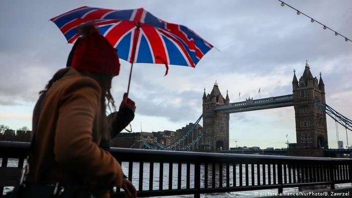 Женщина идет по Лондону с зонтом, окрашенным в цвета британского флага