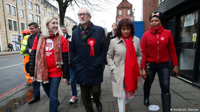 Labour leader Jeremy Corbyn walks down the sidewalk with his wife and supporters (Reuters/L. Niesner)