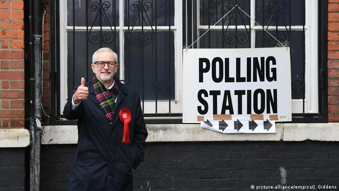 Jeremy Corbyn gestures at a camera near a polling station sign
