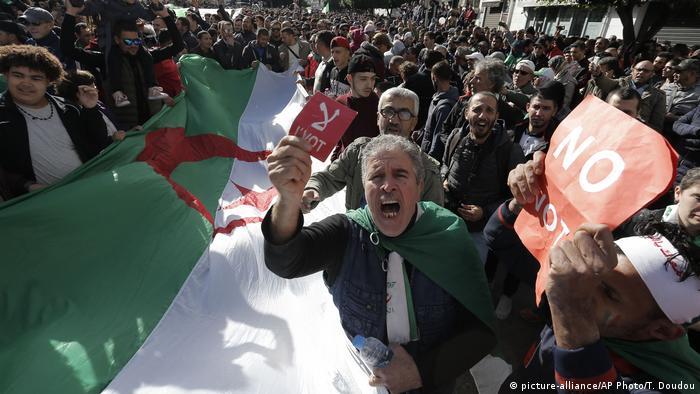 Протестующие в Алжире несут национальный флаг