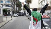 An Algerian demonstrator gestures towards security forces as people take to the streets in the capital Algiers to reject the presidential elections, in Algeria, Thursday, Dec. 12, 2019. Five candidates have their eyes on becoming the next president of Algeria _ without a leader since April _ in Thursday's contentious election boycotted by a massive pro-democracy movement. (AP Photo) |