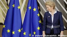 Ursula von der Leyen stands next to EU flags at the EU summit (picture-alliance/AP/O. Matthys)