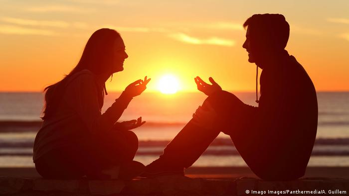 Foto dua orang duduk dipantai dan bercakap-cakap saat matahari terbenam