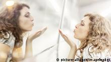 Frau bläst einen Kuss auf ihr Spiegelbild, Kempten, Allgäu, Schwaben, Bayern, Deutschland, Europa | Verwendung weltweit, Keine Weitergabe an Wiederverkäufer.