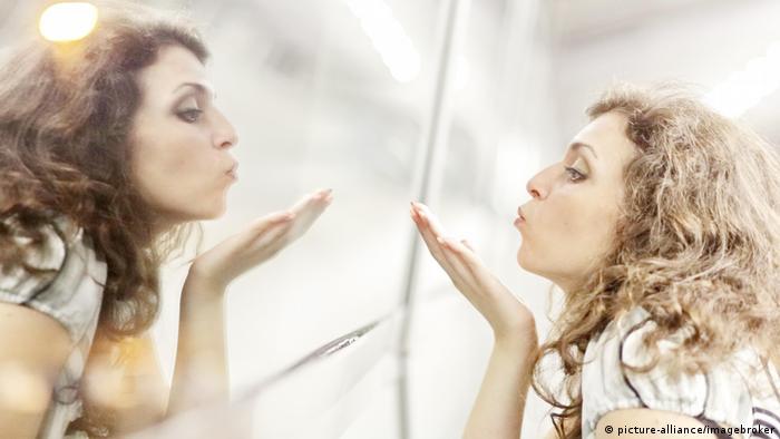 Frau bläst einen Kuss auf Spiegelbild