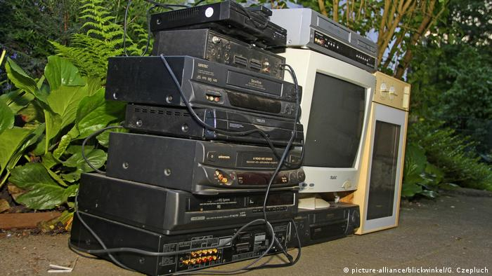 Stack of old DVD players beside discarded monitors