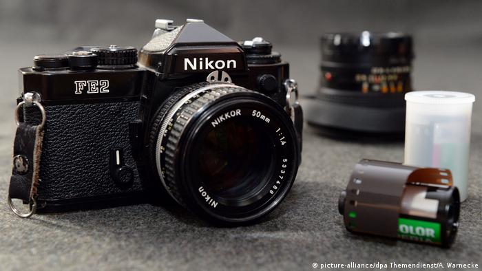 Analog Nikon camera with a roll of film beside it