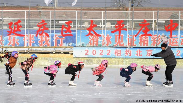 Дети тренируются на фоне олимпийской символики