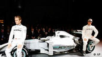 German Formula One drivers Nico Rosberg and Michael Schumacher pose in front of a F1 racecar