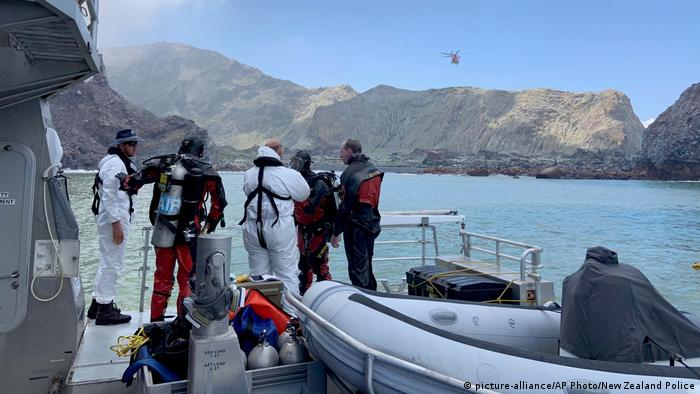 Divers get suited up on the edge of a boat as they prepare to look for White Island victims