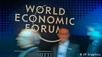 Participants pass sign at the World Economic Forum in Davos, Switzerland