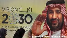 People walk past a banner showing Saudi Crown Prince Mohammed bin Salman, outside a mall in Jiddah, Saudi Arabia, Friday, Dec. 6, 2019. Arabic reads, vision of 2030. (AP Photo/Amr Nabil)  