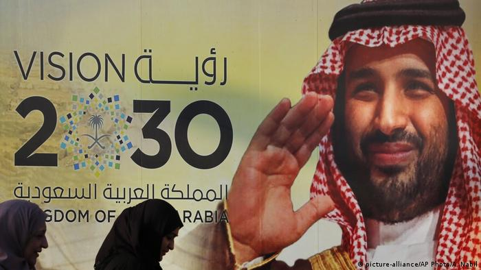 Vision 2030 in letters on the wall of a building with the face of the Crown Prince Mohammed bin Salman (picture-alliance/AP Photo/A. Nabil)