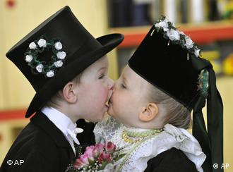Two young children, dressed in traditional Sorbian wedding clothes, kiss each other during a Sorbian celebration
