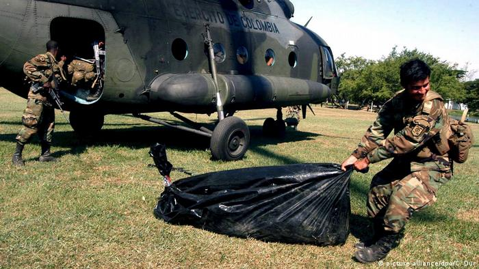 A Colombian soldier drags a bag containing the body of a FARC rebel