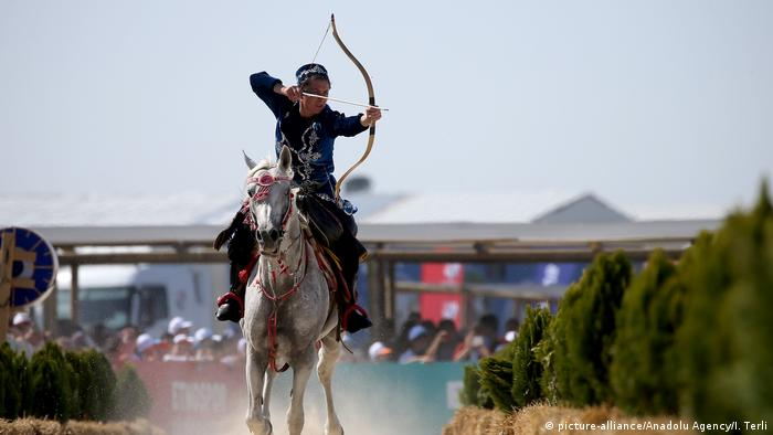 An archer on horseback performs traditional Turkish archery techniques.
