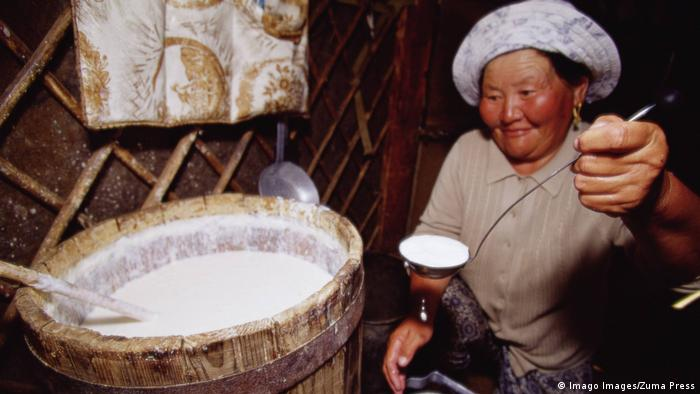 A Mongolian woman serves traditionally prepared Airag, a fermented drink made from mare's milk.