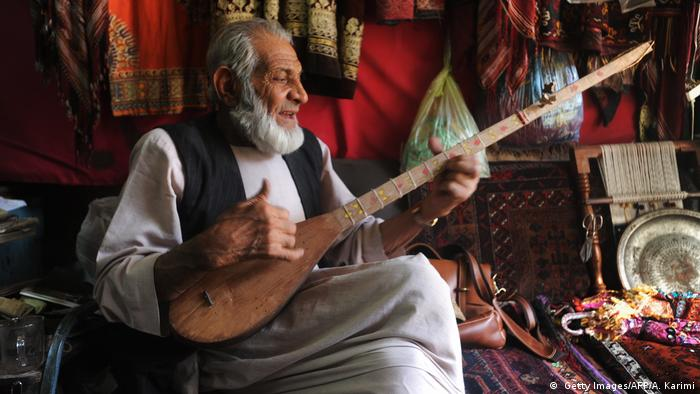 A man plays a dutar, a two-stringed instrument found in Iran.